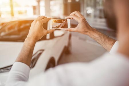 若い男は、車屋で新車を選択して、スマート フォンで写真をです。