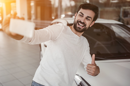 Young man is choosing a new vehicle in car dealership and making photo on a smartphone. Stockfoto