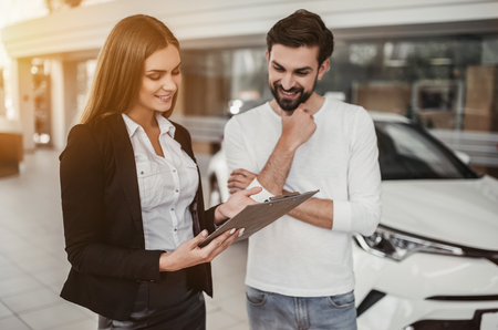 customer service representative: Professional salesperson during work with customer at car dealership. Stock Photo