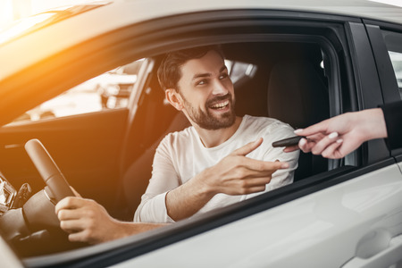 customer service representative: Professional salesperson during work with customer at car dealership. Giving keys to new car owner.