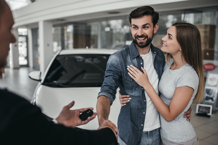 Happy beautiful couple is choosing a new car at dealership.