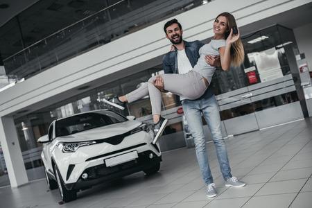 これは新車です!幸せな美しいカップルは、ディーラーで彼らの選択をしました。