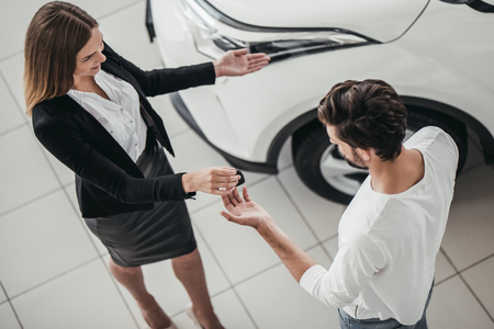 Professional salesperson during work with customer at car dealership. Stock Photo