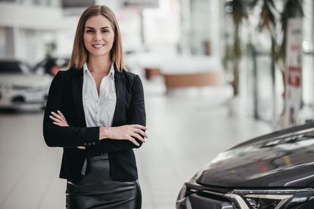Professional female salesperson at car dealership.