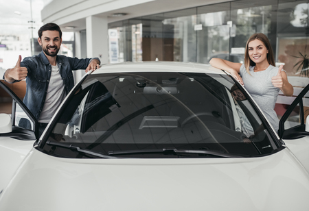 Happy beautiful couple is choosing a new car at dealership, smiling, looking at the camera and showing thumbs up.