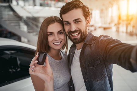 Happy beautiful couple is choosing a new car at dealership. Man is making photo while woman is taking keys in hand.