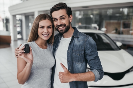 Happy beautiful couple is choosing a new car at dealership, smiling and looking at camera.