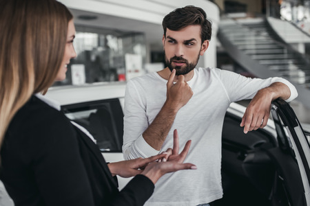 customer service representative: Professional salesperson during work with customer at car dealership. Naming all the benefits of new vehicle.