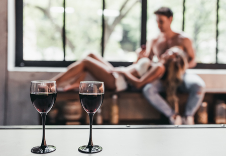 adult sex: Attractive passionate couple on kitchen. Two glasses of wine on the foreground.