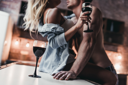 Cropped image of attractive passionate couple on kitchen face to face.