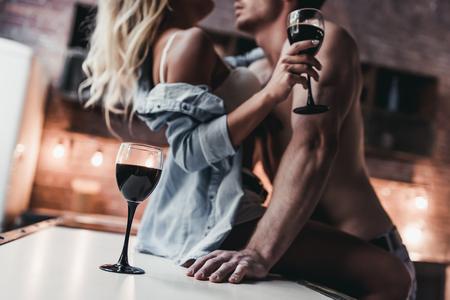 Geerntetes Bild von attraktiven leidenschaftlichen Paaren auf Küche vertraulich. Standard-Bild - 83407571