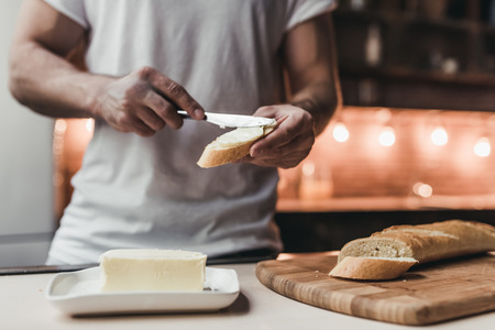 Cropped image of handsome man on kitchen is smearing butter on bread.