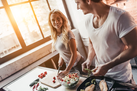 Attractive couple is cooking on kitchen. Looking on each other and smiling.