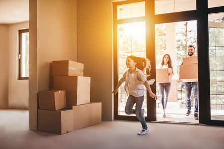Happy family with cardboard boxes in new house at moving day. Stockfoto
