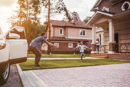 Família feliz. Papai voltou para casa, a filha está correndo para encontrá-lo enquanto a esposa está esperando no alpendre da casa.