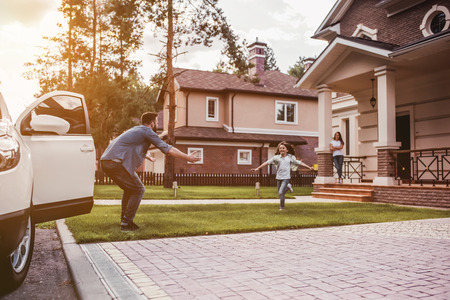 Familia feliz. Papá llegó a casa, su hija corre a buscarlo mientras su esposa está esperando en el porche de la casa. Foto de archivo - 83539474
