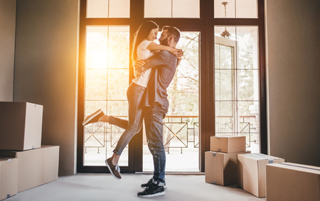 Happy couple with cardboard boxes in new house at moving day. Banque d'images