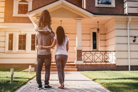 幸せな家族の背面図は現代家の近くに立っています。