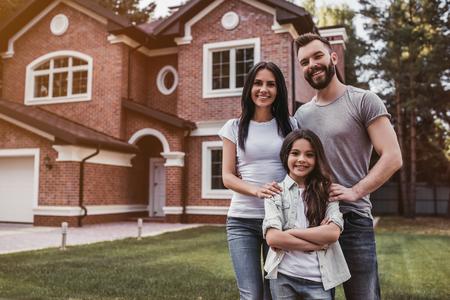 Gelukkige familie staat in de buurt van hun moderne huis, lacht en kijkt naar de camera. Stockfoto