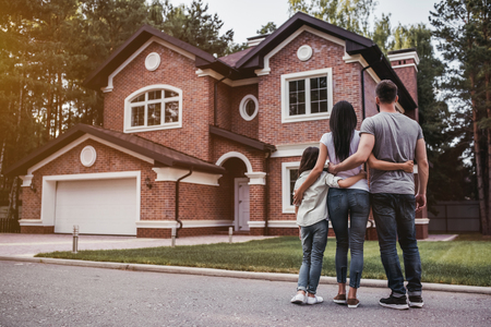 Back view of happy family is standing near their modern house and hugging Foto de archivo
