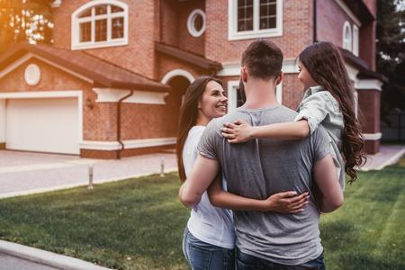 Vista posterior de la familia feliz está de pie cerca de su casa moderna y abrazos