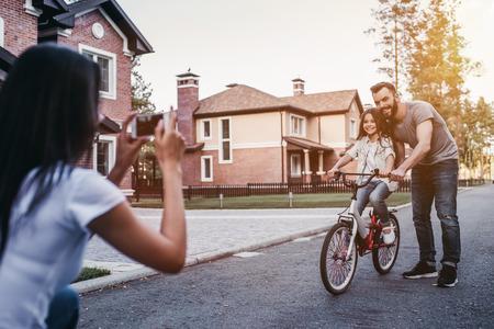 아빠는 자전거를 타는 딸을 가르치고 있습니다. 어머니는 스마트 폰에서 사진을 찍고있다. 스톡 콘텐츠