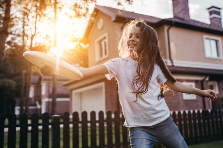 Het mooie meisje speelt, heeft pret en glimlacht op de binnenplaats op de zonsondergang. Stockfoto