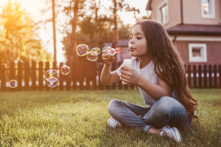 Pretty little girl is sitting on the green grass on the backyard and blowing soap bubbles. Having fun on the sunset.