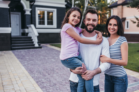 Happy family is standing near their modern private house, smiling and looking at camera. Stock Photo