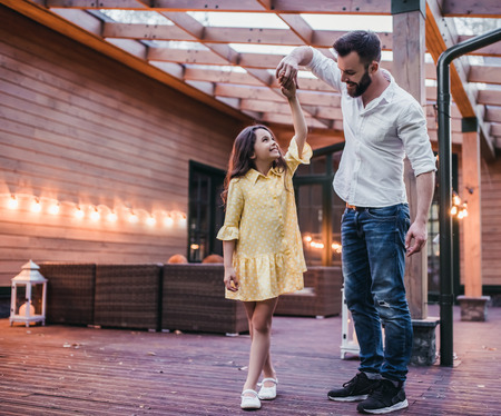 Dad is dancing with his daughter on houses terrace. Stock Photo