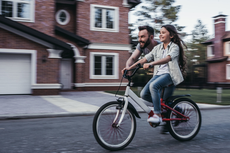 Dad is teaching daughter how to ride bicycle near their private house.