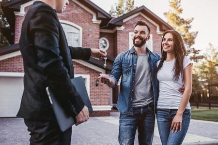 幸せなカップルは、ブローカーと笑顔から彼らの新しい家からキーを取っています。 写真素材