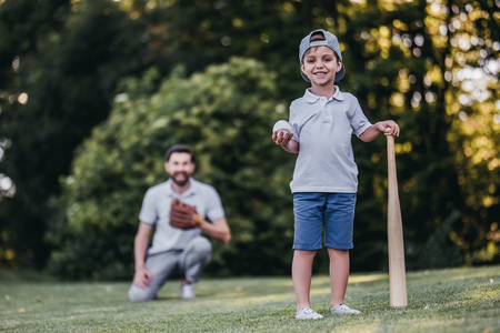 Handsome dad with his little cute sun are playing baseball on green grassy lawn Banco de Imagens - 83434246