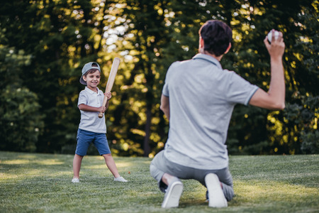 Handsome dad with his little cute sun are playing baseball on green grassy lawn Фото со стока