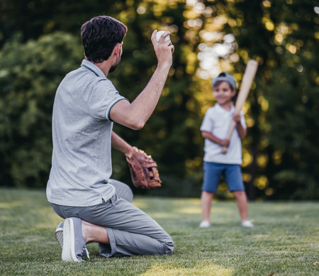 Handsome dad with his little cute sun are playing baseball on green grassy lawn 스톡 콘텐츠