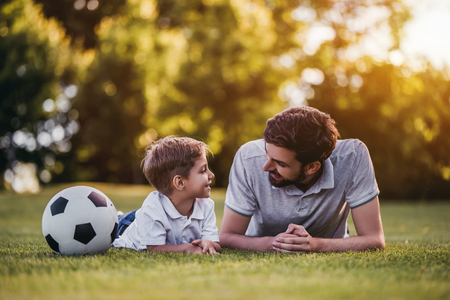 Handsome dad with his little cute sun are playing football on green grassy lawn Stock Photo