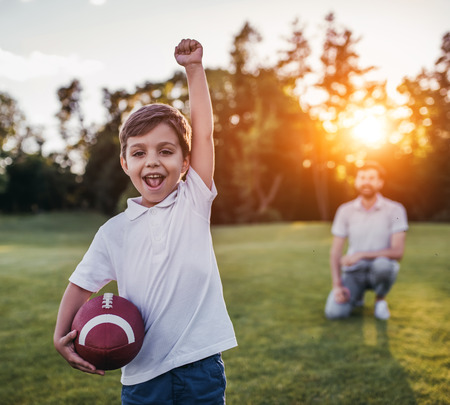 Handsome dad with his little cute sun are having fun and playing American football on green grassy lawn Stockfoto