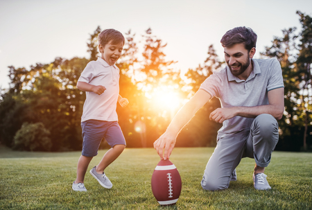 Handsome dad with his little cute sun are having fun and playing American football on green grassy lawn Фото со стока