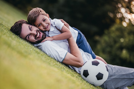 Handsome dad with his little cute sun are having fun and playing football on green grassy lawn