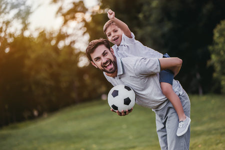 Handsome dad with his little cute sun are having fun and playing football on green grassy lawn Фото со стока - 83435398