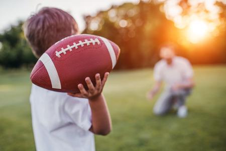 Pai bonito com seu pequeno sol fofo está se divertindo e jogando futebol americano no gramado verde Foto de archivo - 83435422