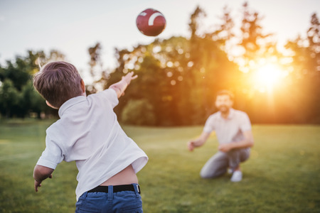Handsome dad with his little cute sun are having fun and playing American football on green grassy lawn Foto de archivo