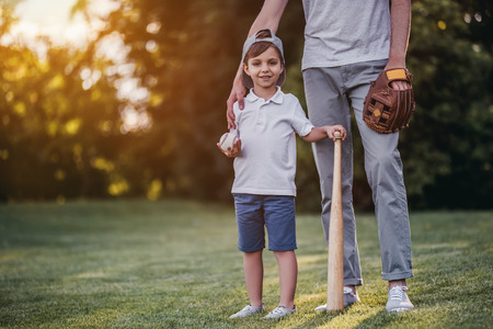 Handsome dad with his little cute sun are playing baseball on green grassy lawn Banque d'images