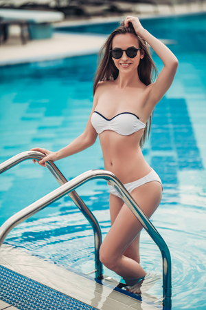 Beautiful young woman in swimsuit and sunglasses is standing on the stairs while exiting the swimming pool.
