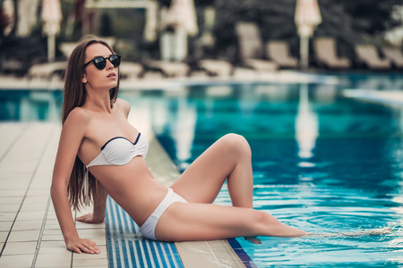 Beautiful young woman in swimsuit and sunglasses is sitting on the swimming pool border with legs lowered in water.