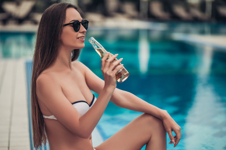 near beer: Beautiful young woman in swimsuit and sunglasses is sitting on the swimming pool border and drinking beer.