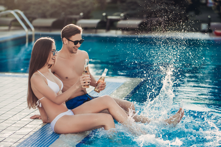 near beer: Young couple is having rest near swimming pool. Having fun together, drinking beer and smiling.