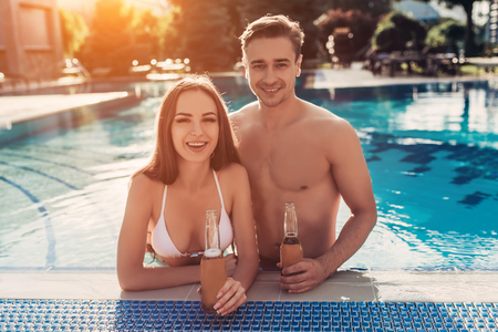 Young beautiful romantic couple is having rest in swimming pool, enjoying the company of each other, drinking beer, smiling and looking at the camera.