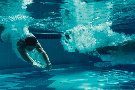Men are jumping into the swimming pool. Men are swimming under water in swimming pool.