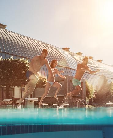 Jonge vrienden hebben samen plezier. Springen in het zwembad.